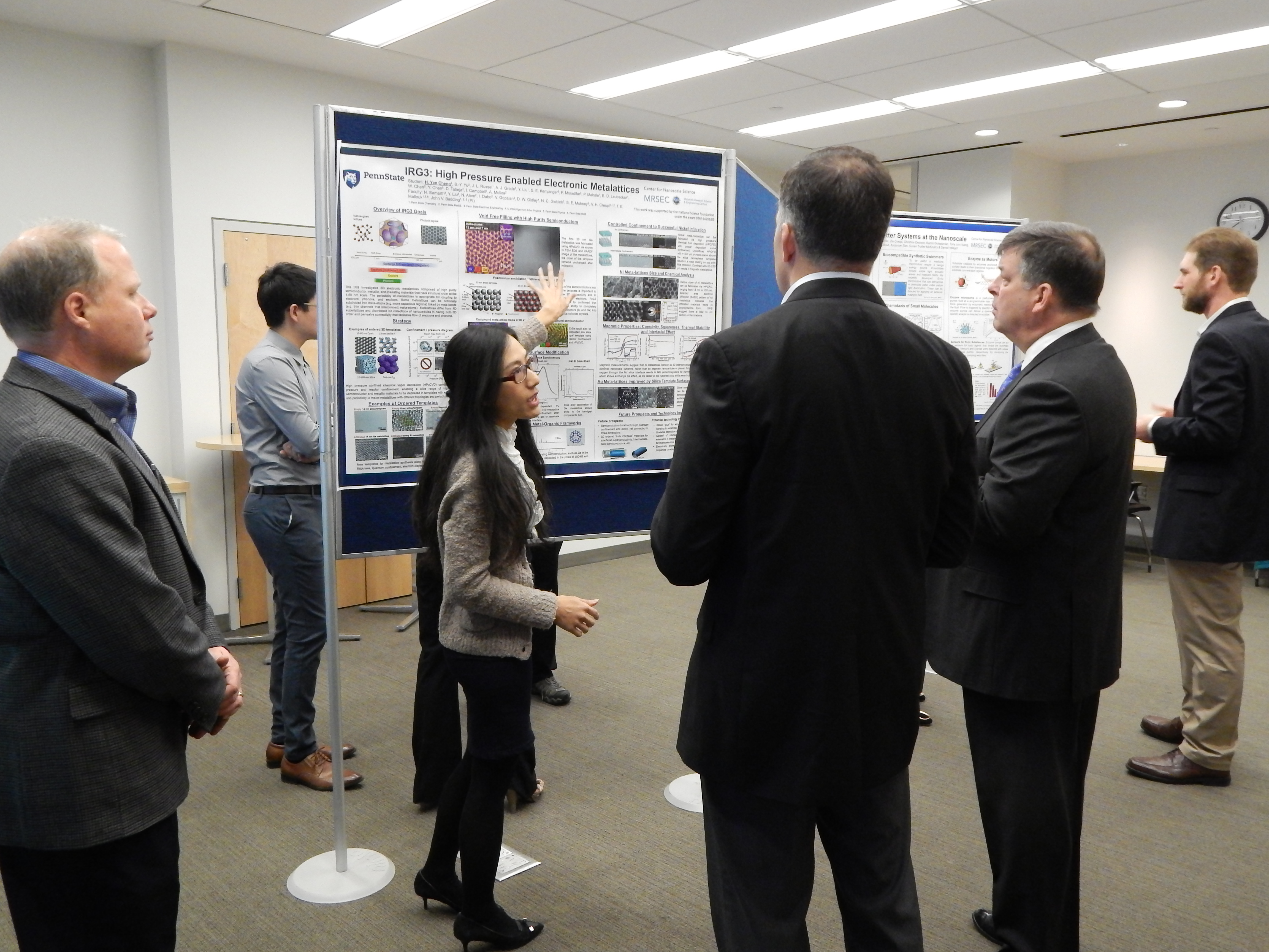 Graduate student explains her research poster to industry representatives
