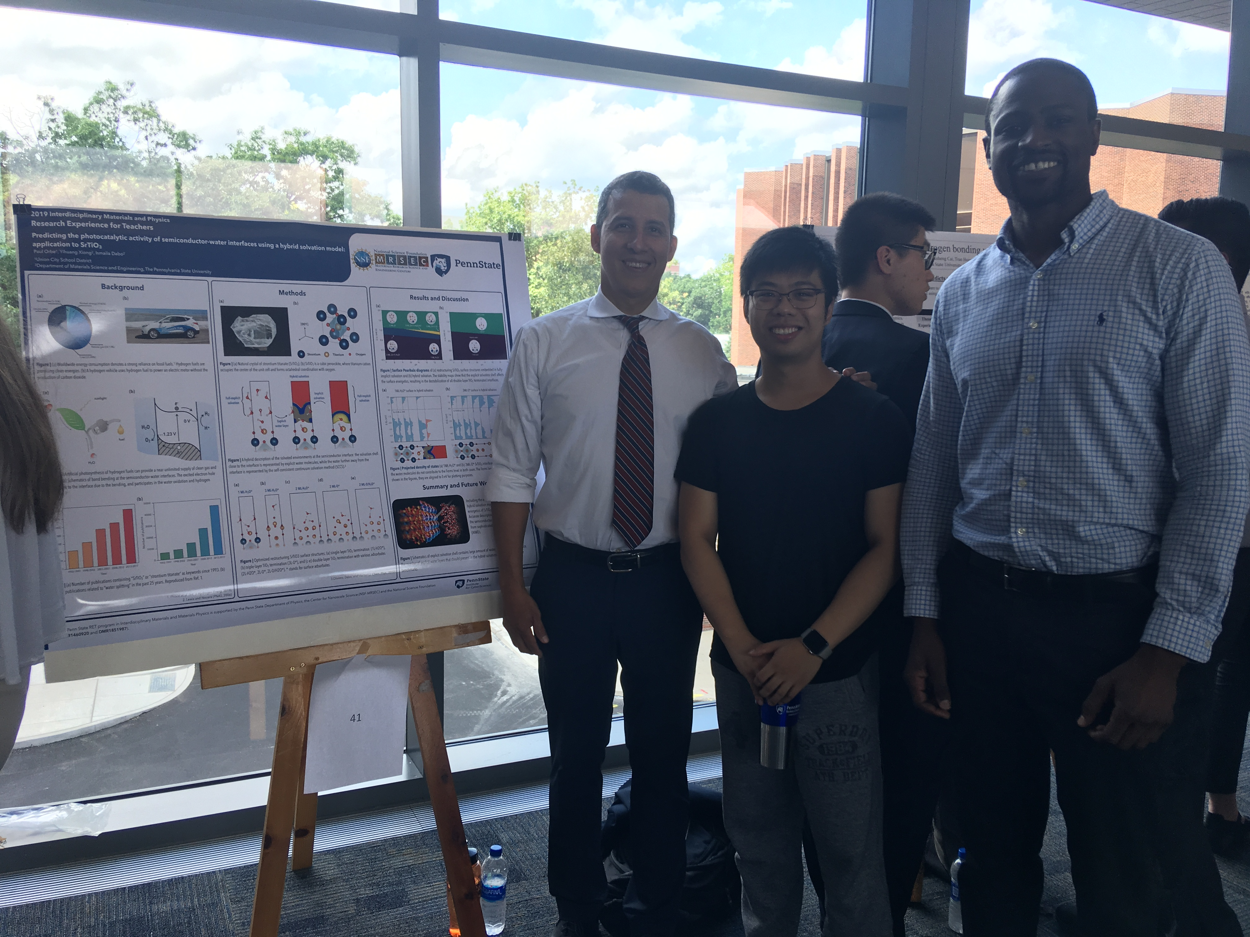 teachers present their research projects at a large symposium with other summer researchers